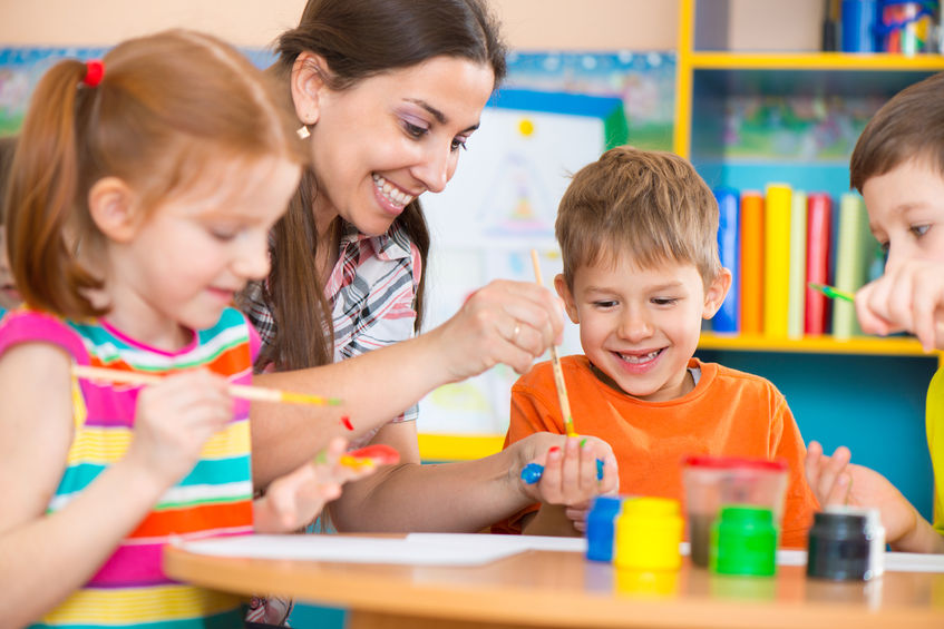 28423236-Cute-little-children-drawing-with-teacher-at-preschool-class-Stock-Photo